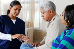 caregiver giving medicines to an old couple